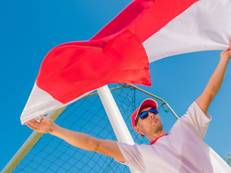 Caucasian Soccer Fan with the Polish Red and White Flag in the Air.